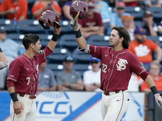 Florida State's Steven Wells (7) congratulates Drew Mendoza (22) following Mendoza's home run during the second inning of an Atlantic Coast Conference NCAA college baseball tournament semifinal against Clemson in Durham, N.C., Saturday, May 26, 2018. (AP Photo/Gerry Broome)