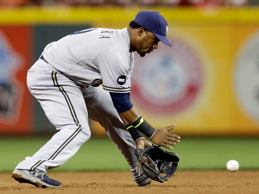Milwaukee Brewers shortstop Jean Segura fields a ground ball hit by Cincinnati Reds' Devin Mesoraco in the fourth inning of a baseball game, Wednesday, Sept. 24, 2014, in Cincinnati. Segura threw Mesoraco out at first. (AP Photo/Al Behrman)