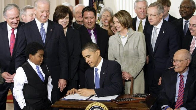 President Obama signs ACA into law in 2010.