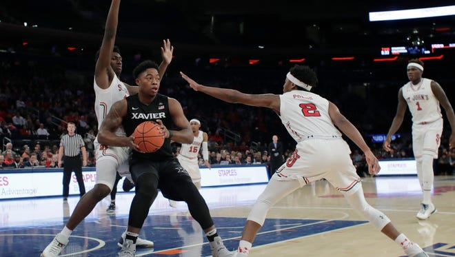 Xavier's Tyrique Jones, center, protects the ball from St. John's Darien Williams, left, and Shamorie Ponds, right, during the first half of an NCAA college basketball game, Sunday, Jan. 29, 2017, in New York.