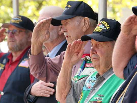 World War II submarine veterans Paul Christopherson (right) and John Baker (center) salute the flag at the beginning of the Tolling The Boats ceremony at Bangor on Thursday.