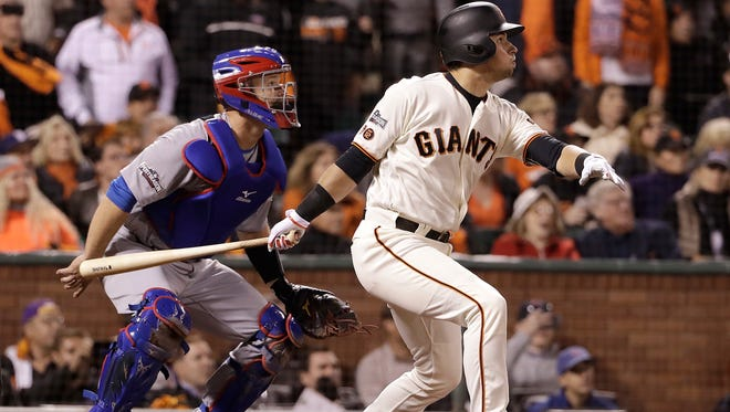 San Francisco Giants' Joe Panik, right, hits a run-scoring sacrifice fly in front of Chicago Cubs catcher David Ross during the fifth inning of Game 4 of the National League Division Series in San Francisco, Tuesday.