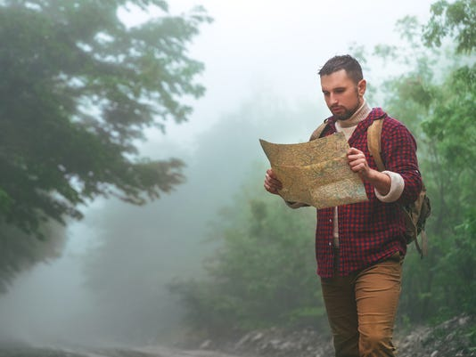 Male tourist in woods in mountains with a map