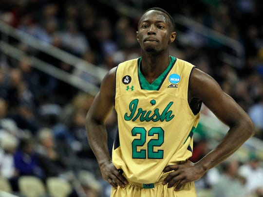 Jerian Grant shows off Notre Dame's third-color alternate uniforms from Under Armour. Along with the gold jerseys with green trim and script team name, the Fighting Irish also sport very green sneakers during the NCAA Tournament.