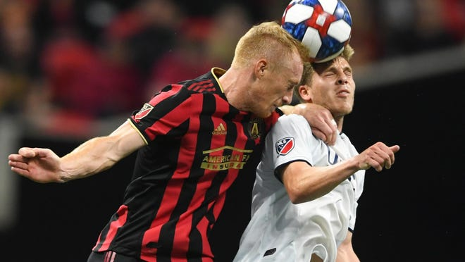 In this Oct. 19, 2019, file photo, Atlanta United defender Jeff Larentowicz, left, and New England Revolution midfielder Scott Caldwell battle for a header during round one of an MLS Cup playoff soccer game in Atlanta.