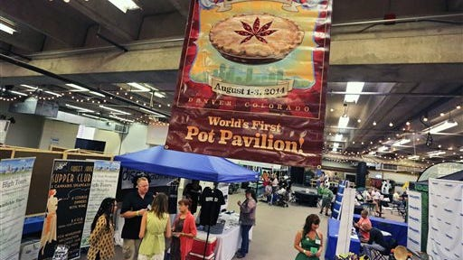 Visitors attend the pot pavilion at Denver County Fair, the nation's first county fair to allow pot competitions, in Denver, today.