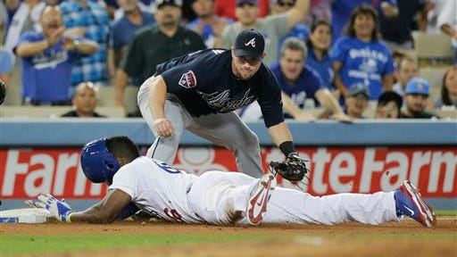 Los Angeles' Yasiel Puig, bottom, slides safely into third base with a triple as Atlanta third baseman Chris Johnson watches during the fifth inning Tuesday in Los Angeles.