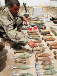 Iraqi army soldiers inspect a cache of weapons found