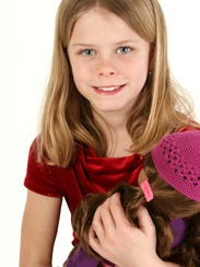 Beautiful young girl holding doll. Shot in studio over