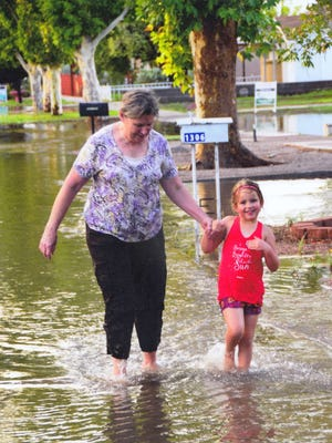 Recent rain storms signal the start of the monsoon season Deming, NM. Beth Stevens and her granddaughter Madison Stevens waited until after a rain storm to wade through large puddles in the neighborhood. Madison is the daughter of Shannon and Joel Stevens of Deming.