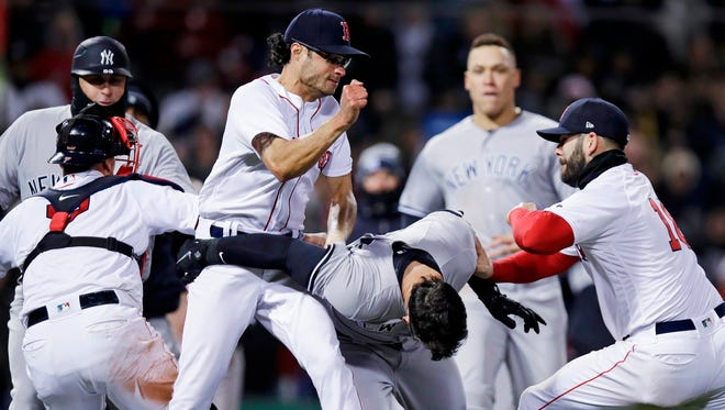 Boston Red Sox relief pitcher Joe Kelly, left, throws a punch at New York Yankees' Tyler Austin, center, as they fight during the seventh inning of a baseball game at Fenway Park in Boston, Wednesday, April 11, 2018. At right is Boston Red Sox first baseman Mitch Moreland.