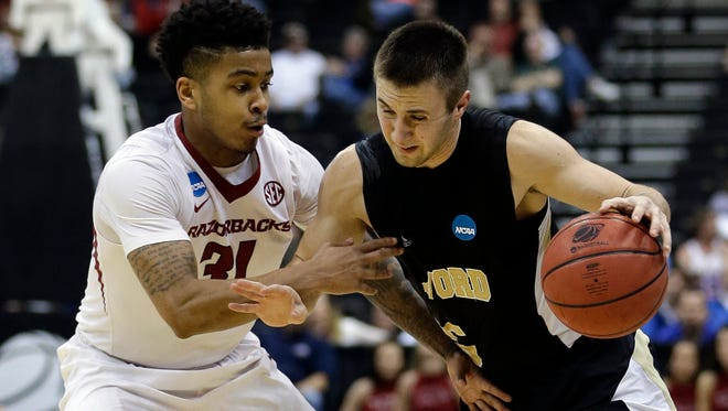 Wofford guard Eric Garcia (5) attempts to get past Arkansas guard Anton Beard (31) during the second half of an NCAA tournament second round college basketball game Thursday, March 19, 2015, in Jacksonville, Fla.