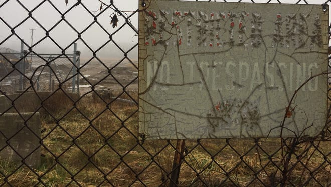 "This faded ""Restricted Area No Trespassing"" sign hangs on a fence around the 40-acre property BWL used as a dump site for its coal ash waste from 1980 to 1997."