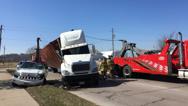 Emergency responders and crews from Big 10 towing work to lift a semi trailer off another vehicle after a rollover crash on the curved portion of South Clinton Street where it meets Kirkwood Avenue on Friday, March 17, 2017.