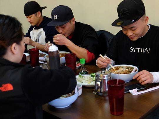 From left, Chor Lor, Phang Lor and Mikey Yang enjoy bowls of pho for lunch at  Pho Tai  in Madison Heights.
