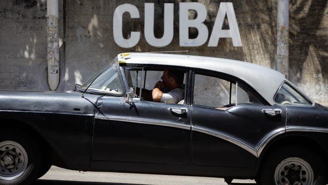 """A man drives his taxi past a Cultural Center with the word """"Cuba"""" on it, in Havana, Cuba, Tuesday, April 14, 2015. President Barack Obama will remove Cuba from the list of state sponsors of terrorism, the White House announced Tuesday, a key step in his bid to normalize relations between the two countries. (AP Photo/Desmond Boylan)"""