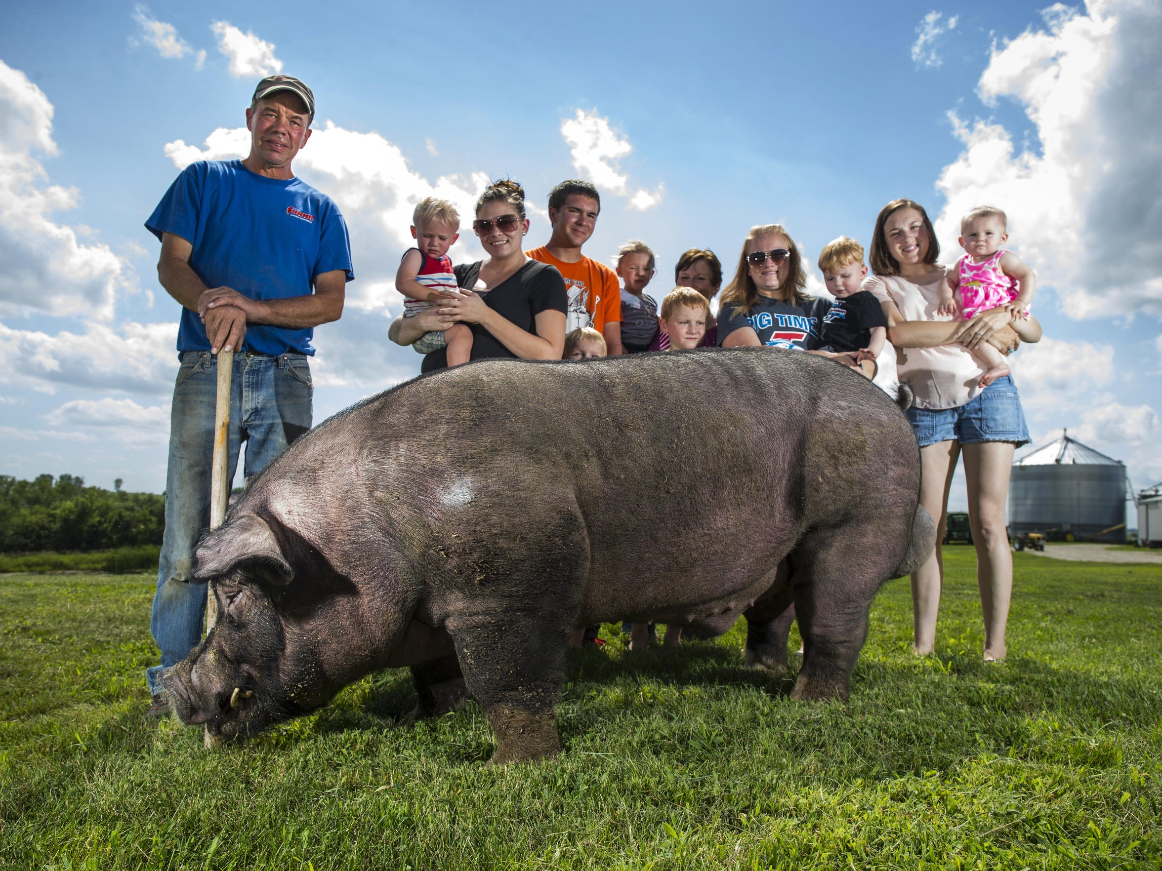 """Turbo Charge"", a boar owned by Steve and Dara Queck of rural Peru, poses with his family."