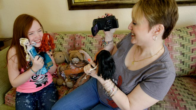 """Gracie Hunter, left, and her Mom, Melissa, make a video for a doll review while on vacation in Kissimmee, Fla. The mother-daughter duo, stars of the """"Mommy and Gracie"""" YouTube show, review dolls for kids."""