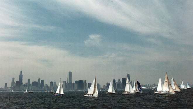 Sailboats cross the Chicago skyline at the start of the 90th Chicago-to-Mackinac Island yacht race on Lake Michigan in this file photo.