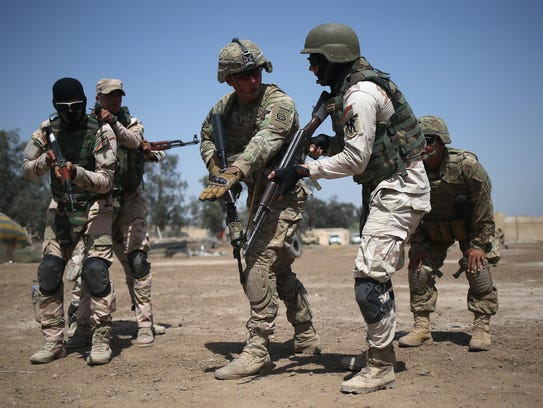 Army trainers instruct Iraqi Army recruits at a military