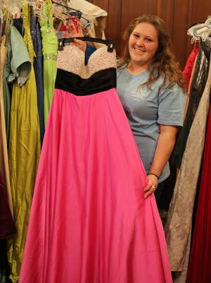 Howard Payne University student Sierra Spruill of Ranger holds a prom dress available to Brownwood area high school students for free during the university's Cinderella Project, which provides gowns free to students to wear to prom.
