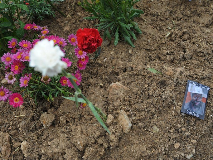"""Flowers and a card that reads """"Your suffering is our suffering"""" lie on the grave of a victim of the mine accident in Soma, Turkey."""