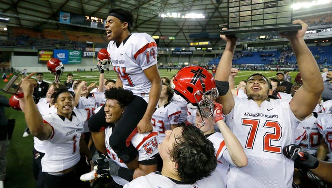 Archbishop Murphy's Abraham Lucas (right) holds the Class 2A state championship trophy aloft in December at the Tacoma Dome. Lucas signed Wednesday with Washington State.
