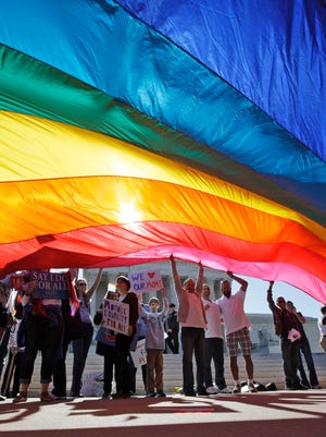 Gay marriage supporters wave a huge flag in front of the United States Supreme Court Tuesday morning in Washington DC.