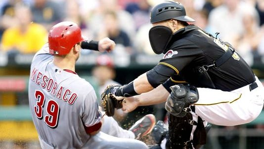 Cincinnati Reds catcher Devin Mesoraco (39) slides into home plate as Pittsburgh Pirates catcher Russell Martin (55) attempts a force out. Mesoraco was originally called out on the play but the ruling was overturned on an umpire review during the third inning at PNC Park.