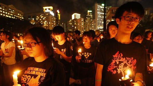 Young participants hold candles as they join tens of thousands of people attending a candlelight vigil at Victoria Park in Hong Kong on June 4, 2014, to mark the 25th anniversary of the June 4 Chinese military crackdown on the pro-democracy movement in Beijing.