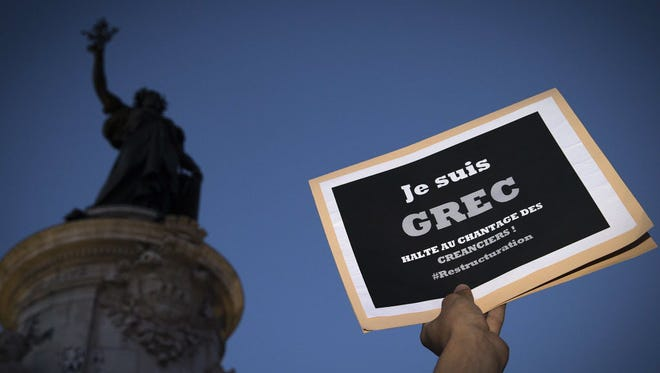 """A person holds a banner that reads, """"I am a Greek, stop (the) blackmail creditors"""" during a rally in support of the people of Greece  in Paris on July 5, 2015."""