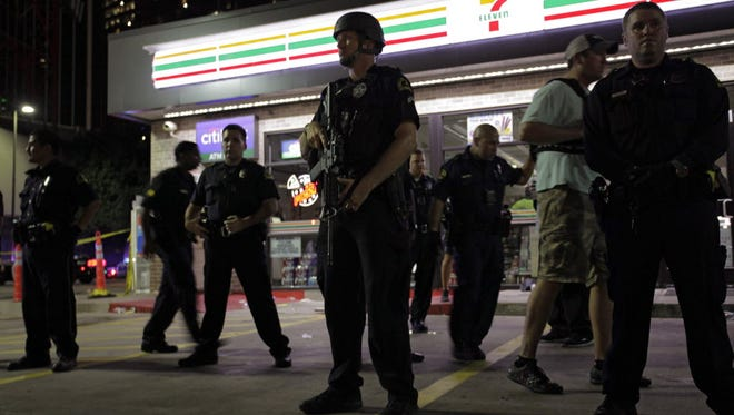 Police face protesters in downtown Dallas after 11 police were shot.
