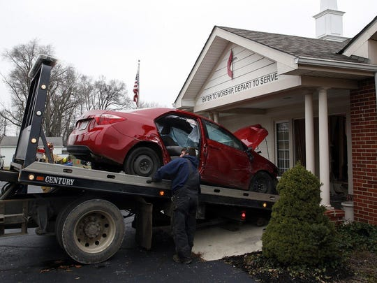 A car that crashed into the entrance of the Crossroads United Methodist Church is towed out of the doorway on Sunday.