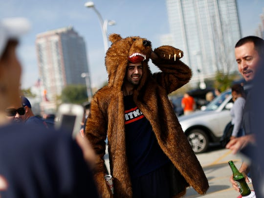 A Chicago Bears fan roams around in a bear costume while tailgating before Sunday's game at Soldier Field in Chicago.