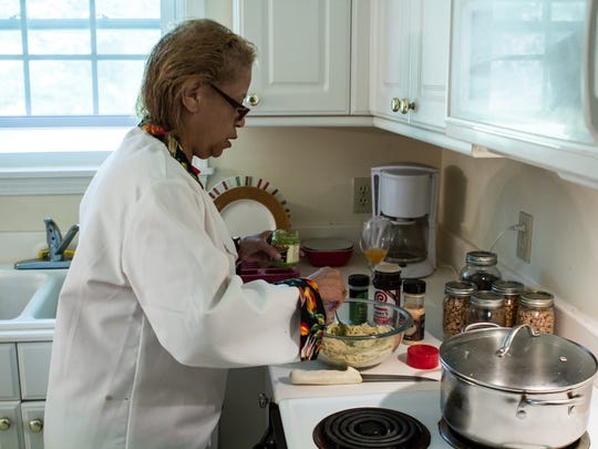 Cookbook author Cassandra Harrell mixes pesto into a cold spaghetti salad at her home in Jackson.