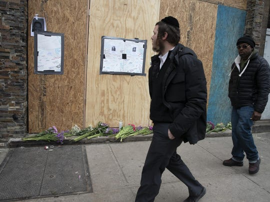 """FILE - In this Friday, Dec. 13, 2019, file photo, men pass a boarded-up kosher grocery store, in Jersey City, N.J., where three people and two gunmen were killed days earlier. New York Mayor Bill de Blasio called the incident a """"premeditated anti-Semitic hate crime."""" (AP Photo/Mark Lennihan, File)"""