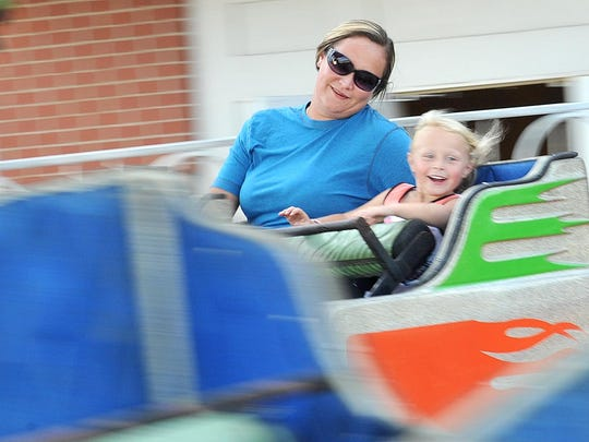 Amber Adams and Ashley Smith take a ride on one of the attractions Wednesday evening during the first day of the Bellville Street Fair.
