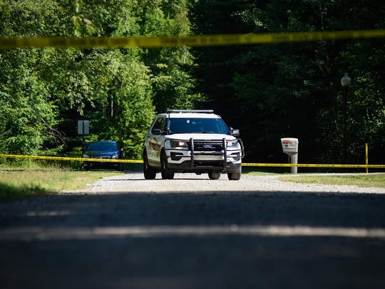 A police vehicle sits outside the scene of a death