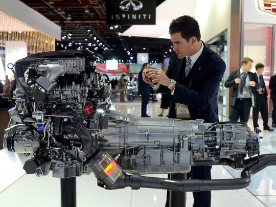 An event goer takes photos of an engine Tuesday, Jan. 12, during the North American International Auto Show at Cobo Hall.
