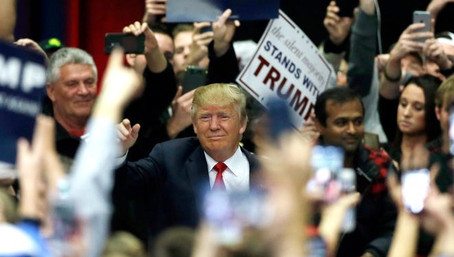 Republican presidential candidate businessman Donald Trump enters a rally before addressing supporters at a campaign rally, Monday, Dec. 21, 2015, in Grand Rapids, Mich. (AP Photo/Carlos Osorio)