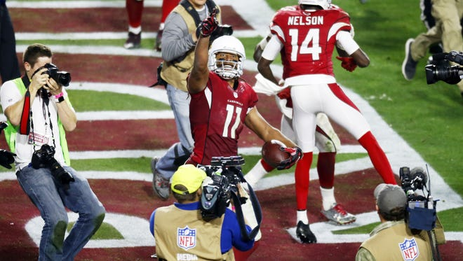 Cardinals receiver Larry Fitzgerald celebrates the game winning touchdown against the Packers in overtime during the NFC Divisional playoff game at University of Phoenix Stadium in Glendale on Saturday, January 16, 2015.