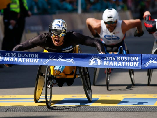 Apr 18, 2016; Boston, MA, USA; Marcel Hug of Switzerland crosses the finish line just in front of Ernst Van Dyk of South Africa and Kurt Fearnley of Australia in the 120th Boston Marathon. Mandatory Credit: Greg M. Cooper-USA TODAY Sports