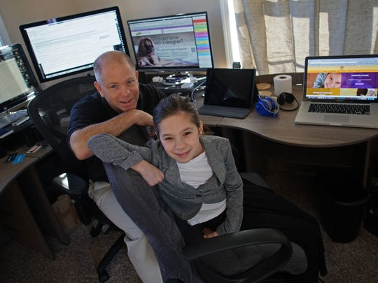 Mike Fox sits with his 10-year-old daughter, Arianna Fox, who is a junior marketer for her parents' company, Splash Designworks in Milford.