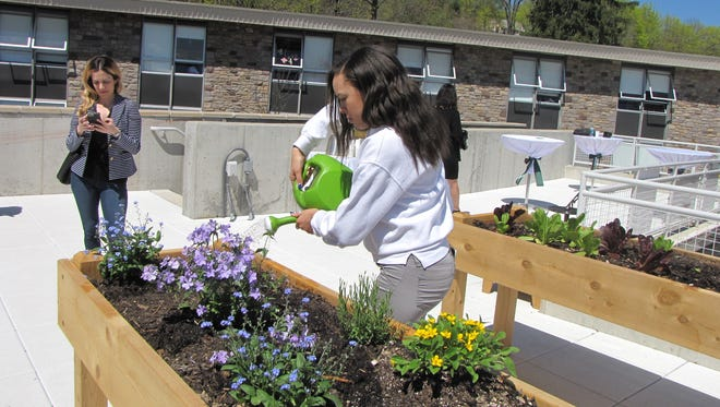 "Montclair Kimberley Academy student Micaiah Lewis waters one of the garden beds on the school's ""Green Roof,"" which officially opened on April 18."