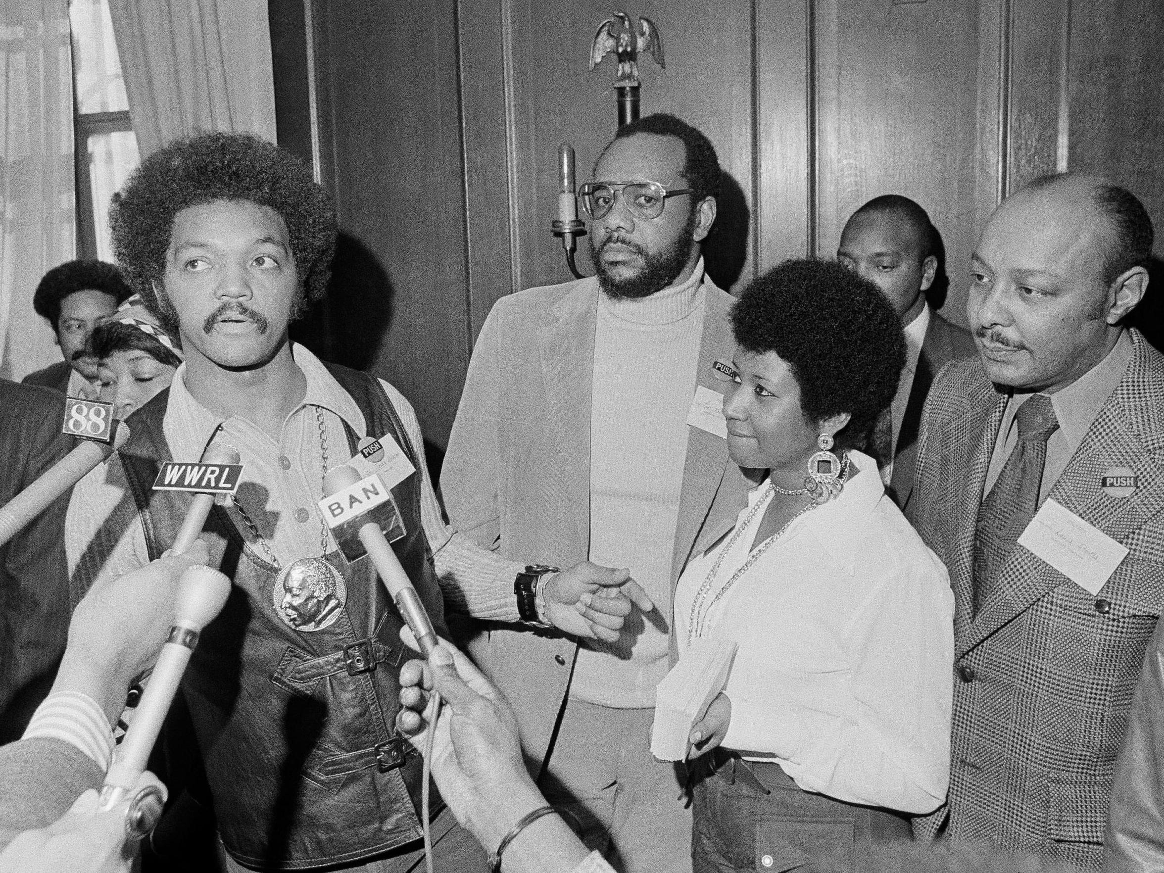 On March 26, 1972, the Rev. Jesse Jackson speaks to reporters at the Operation PUSH Soul Picnic in New York with Tom Todd, vice president of PUSH, second left, singer Aretha Franklin and Congressman Louis Stokes, D-Cleveland.