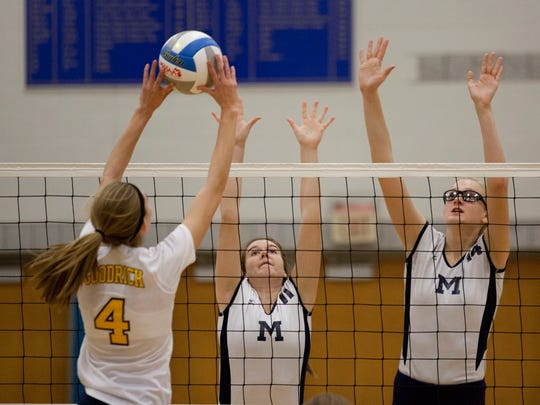 Marysville senior Devan Valko and junior Payton Husson jump to block a spike during a regional final volleyball game Thursday, November 12, 2015 at Imlay City High School.