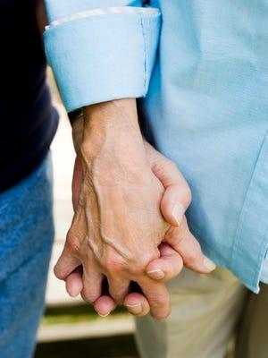 Couple holding hands -- elderly, seniors, aging, longevity.