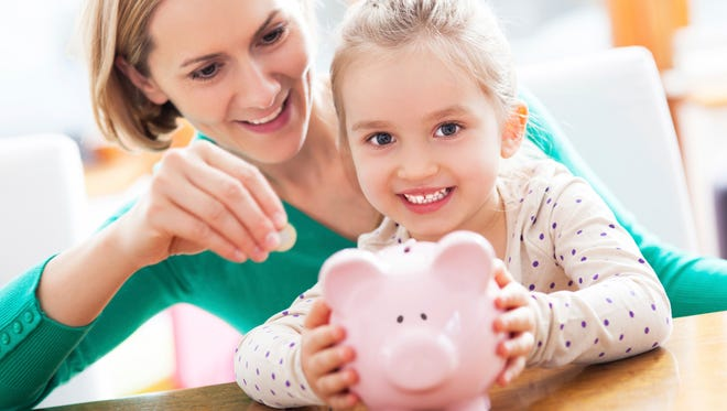 Mother and daughter playing with piggy bank