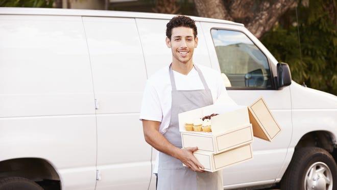 Baker Delivering Cakes Standing In Front Of Van