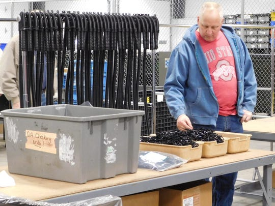 Tom Herman of Bellevue looks through a parts tray at one of the Sandco Industries workstations during Wednesday's open house.